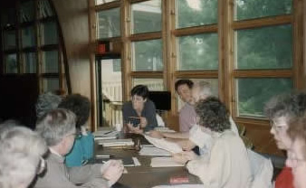 Writers workshop participants discuss manuscript.